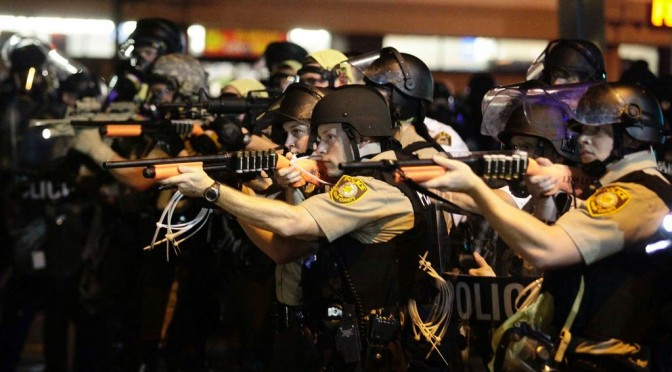 Officers armed with an Assault Rifles, threatening unarmed protesters.